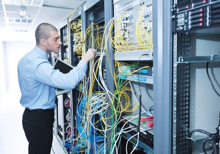 servers: young engeneer business man with thin modern aluminium laptop in network server room