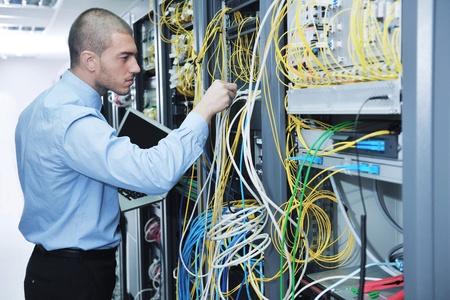 jeune homme d'affaires avec un ordinateur portable engeneer aluminium mince moderne dans la salle de serveur réseau