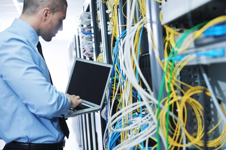 network server: young engeneer business man with thin modern aluminium laptop in network server room
