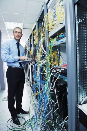 hombre flaco: ingeniero joven hombre de negocios con la computadora port?til delgada de aluminio moderno en la sala de servidores de red