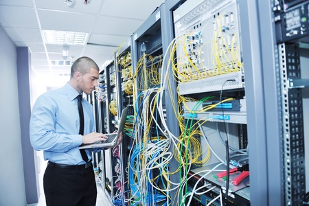 tv network: young engeneer business man with thin modern aluminium laptop in network server room