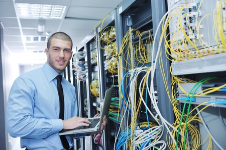 network engineer: young engeneer business man with thin modern aluminium laptop in network server room