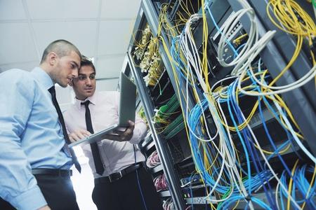 seguridad laboral: grupo de j�venes empresarios que el ingeniero en la sala de servidores de red para resolver problemas y dar ayuda y apoyo
