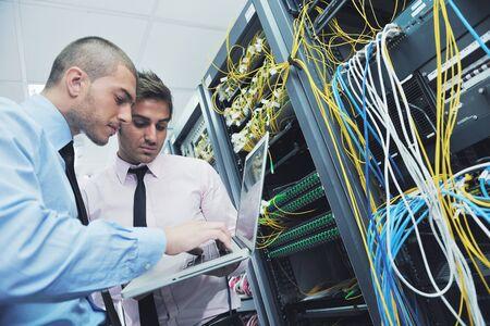 ingeniero: grupo de j�venes empresarios que el ingeniero en la sala de servidores de red para resolver problemas y dar ayuda y apoyo