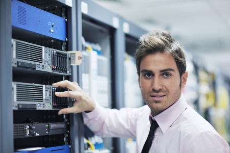 server rack: young handsome business man  engeneer in datacenter server room