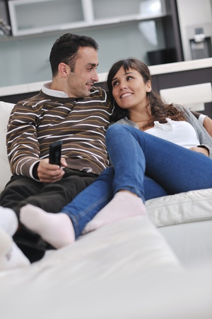 Relaxed young  couple watching tv at home in bright living room Stock Photo - 11133021