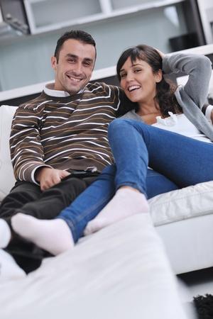 pareja viendo television: Pareja joven relajado viendo la televisión en casa, en luminoso salón Foto de archivo