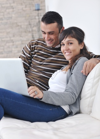 joyful couple relax and work on laptop computer at modern living room indoor home Stock Photo - 11132969