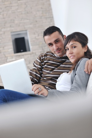 joyful couple relax and work on laptop computer at modern living room indoor home Stock Photo - 11132974