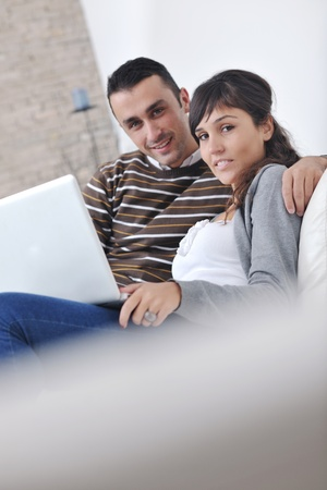 joyful couple relax and work on laptop computer at modern living room indoor home Stock Photo - 11132966