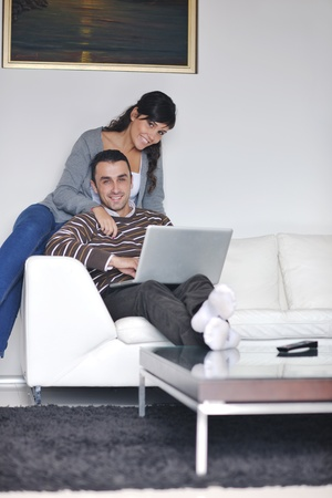 joyful couple relax and work on laptop computer at modern living room indoor home Stock Photo - 11132996