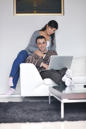 joyful couple relax and work on laptop computer at modern living room indoor home Stock Photo - 11132976