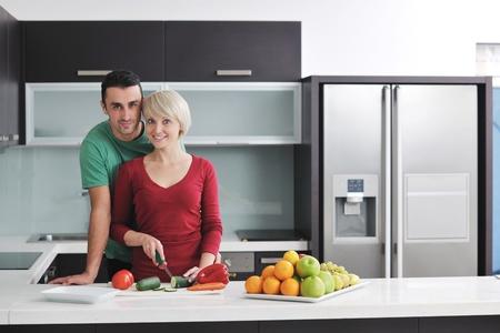 cucina moderna: giovane coppia felice divertirsi in interni moderna cucina durante la preparazione di frutta fresca e verdure cibo insalata