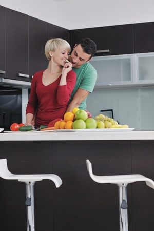 vegetables young couple: happy young couple have fun in  modern kitchen indoor  while preparing fresh fruits and vegetables food salad Stock Photo