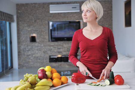 happy young  beautiful blonde  woman prepare food in  the kitchen at home photo