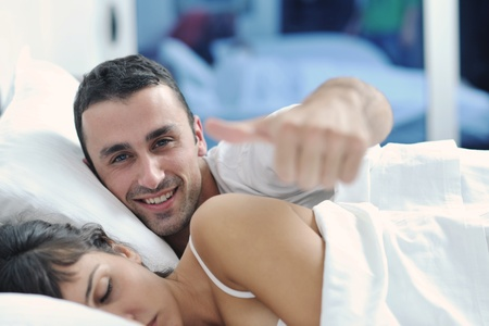 make love: happy young healthy people  couple have good time in their bedroom make love and sleep Stock Photo