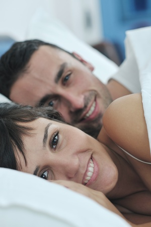 happy young healthy people  couple have good time in their bedroom make love and sleep Stock Photo - 11196429