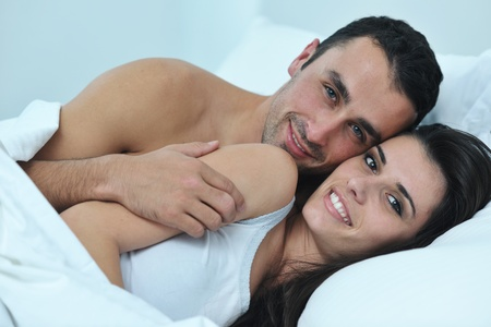 happy young healthy people  couple have good time in their bedroom make love and sleep photo