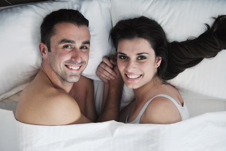 happy young healthy people  couple have good time in their bedroom make love and sleep Stock Photo