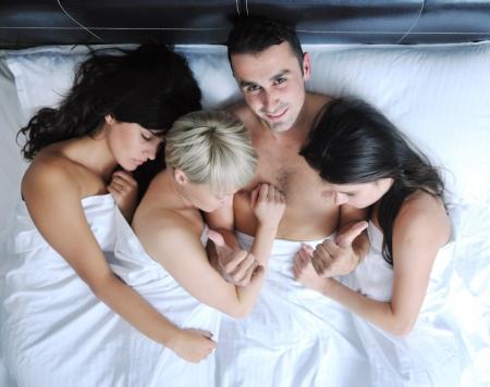 seks: Udane mÅ'ody przystojny mężczyzna w łóżku z trzema miejscami do spania dziewczyn Zdjęcie Seryjne