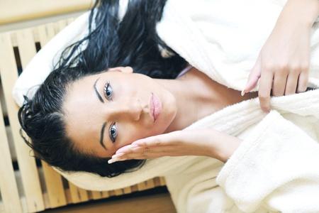sudoracion: Bastante joven mujer tomar un baño de vapor en el tratamiento sauna finlandesa de madera mientras llevaba una toalla blanca