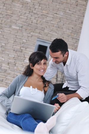 joyful couple relax and work on laptop computer at modern living room indoor home Stock Photo - 11196697