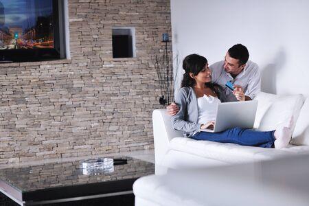 mann couch: freudigen paar entspannen und die Arbeit an Laptop-Computer zu modernen Wohnzimmer Indoor Hause Lizenzfreie Bilder