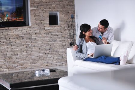 couch: joyful couple relax and work on laptop computer at modern living room indoor home Stock Photo