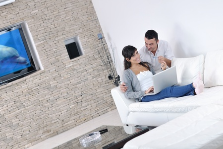internet love: joyful couple relax and work on laptop computer at modern living room indoor home Stock Photo