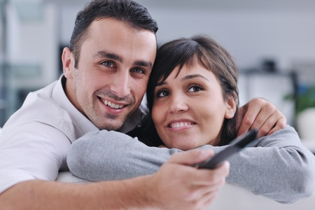Relaxed young  couple watching tv at home in bright living room Stock Photo - 11279167