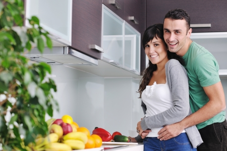 young couple have fun in modern kitchen photo