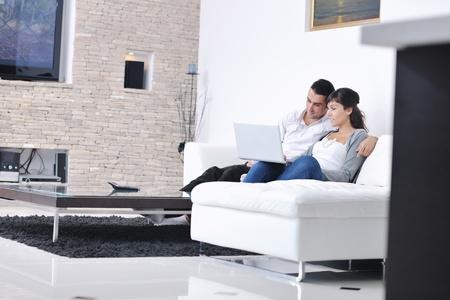 pareja feliz relajarse y trabajar en la computadora port?til en casa moderna sala de estar interior Foto de archivo