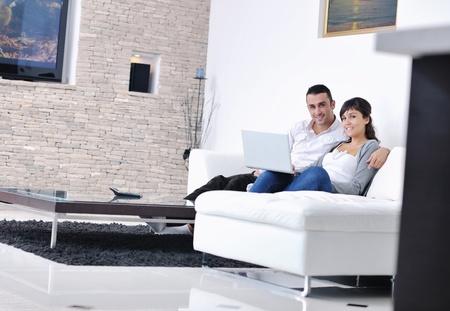 pareja feliz relajarse y trabajar en la computadora portátil en casa moderna sala interior