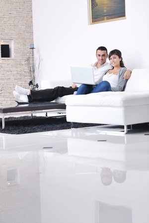 tv home: joyful couple relax and work on laptop computer at modern living room indoor home Stock Photo