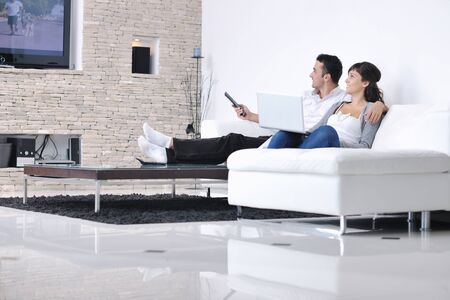 watching tv: Relaxed young  couple watching tv at home in bright living room Stock Photo