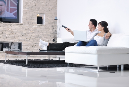 home entertainment: Relaxed young  couple watching tv at home in bright living room Stock Photo