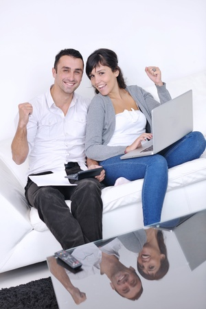 joyful couple relax and work on laptop computer at modern living room indoor home Stock Photo - 11279231
