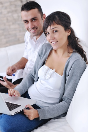 joyful couple relax and work on laptop computer at modern living room indoor home photo
