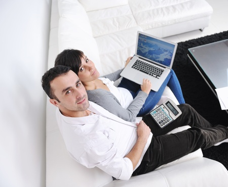 joyful couple relax and work on laptop computer at modern living room indoor home Stock Photo - 11292920