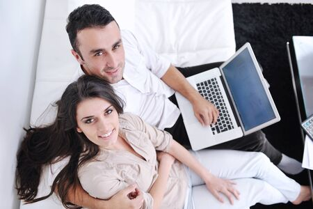 joyful couple relax and work on laptop computer at modern living room indoor home Stock Photo - 11291584