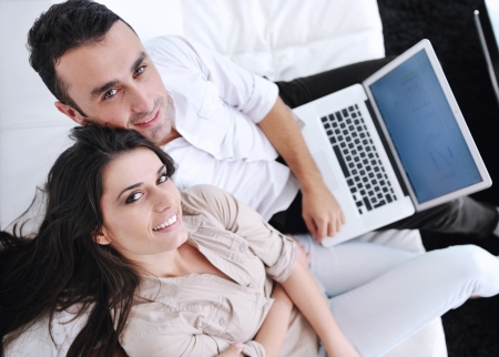 joyful couple relax and work on laptop computer at modern living room indoor home Stock Photo - 11292874