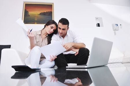 joyful couple relax and work on laptop computer at modern living room indoor home Stock Photo - 11292907