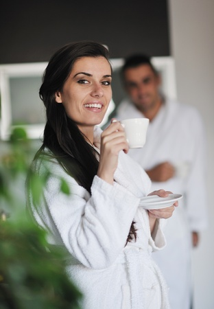 Young love couple taking fresh morning cup of coffee in the modern appartment photo