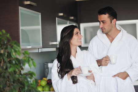 appartment: Young love couple taking fresh morning cup of coffee in the modern appartment Stock Photo