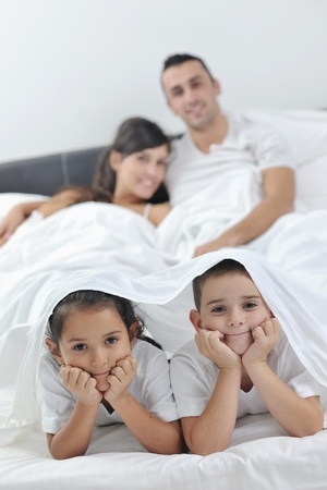 happy young Family in their bedroom have fun and play in bed photo