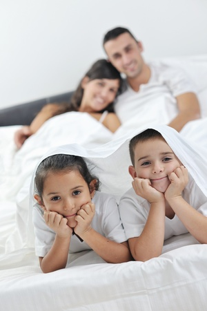 happy young Family in their bedroom have fun and play in bed Stock Photo - 11292910