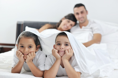 happy young Family in their bedroom have fun and play in bed Stock Photo - 11292854