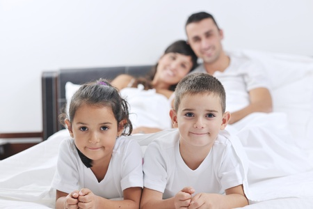 happy young Family in their bedroom have fun and play in bed Stock Photo - 11292848