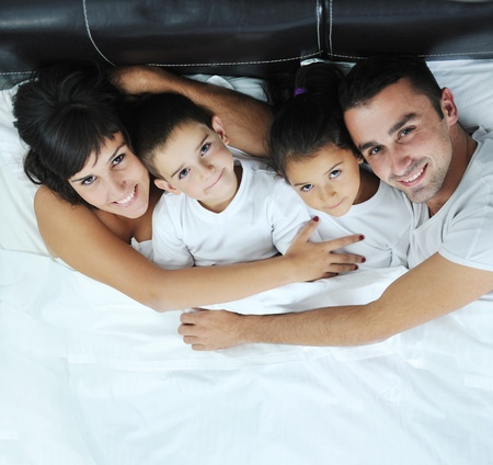 happy young Family in their bedroom have fun and play in bed Stock Photo - 11279207
