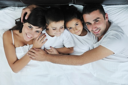 happy young Family in their bedroom have fun and play in bed Stock Photo - 11279324